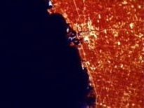 Satellite view showing red heat coming off of dense human development along coastline